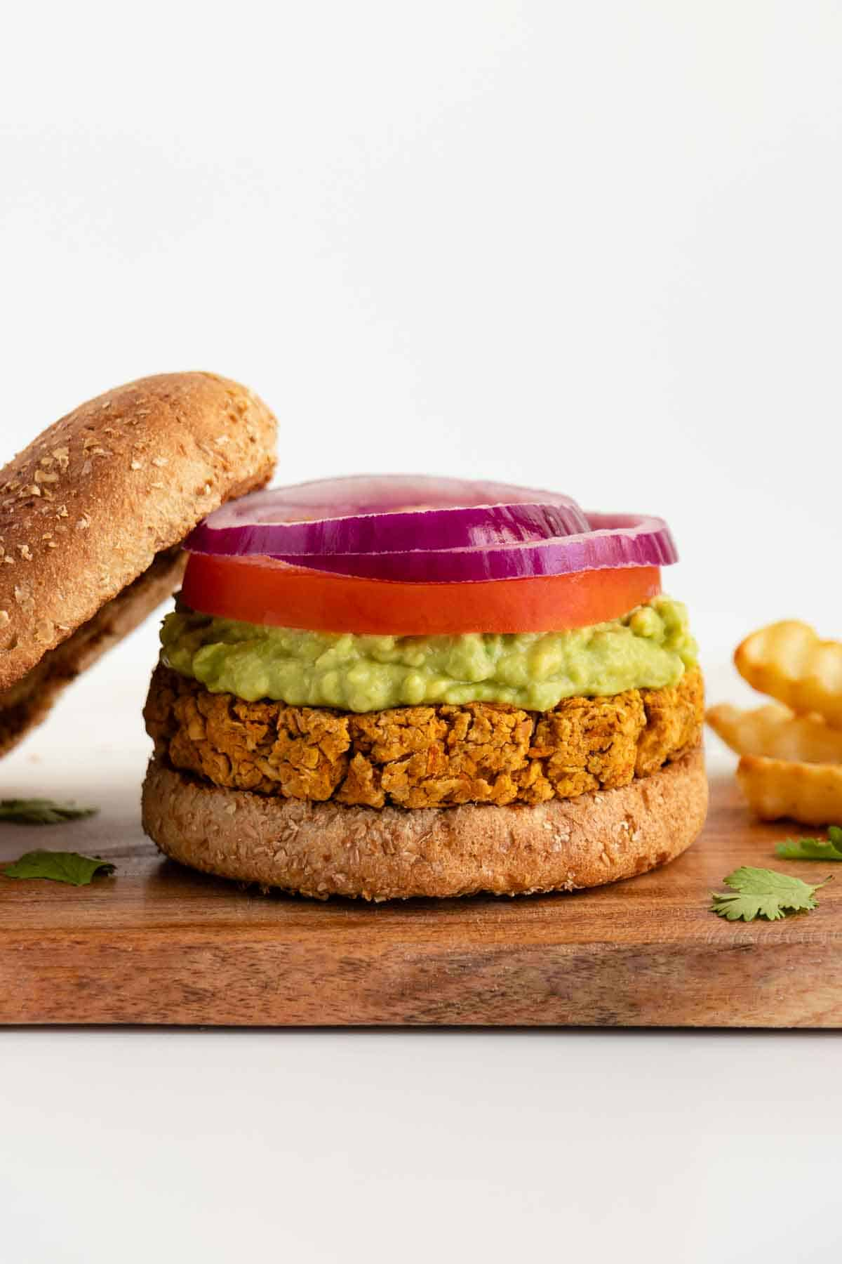 a vegan chickpea burger patty on a bun with mashed avocado, tomato, and sliced red onion