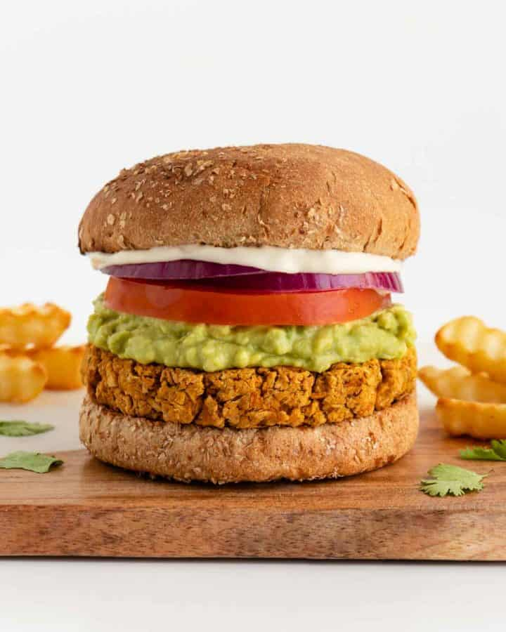 a vegan chickpea burger between two buns with mashed avocado, tomato, red onion, and mayo surrounded by crinkle cut french fries