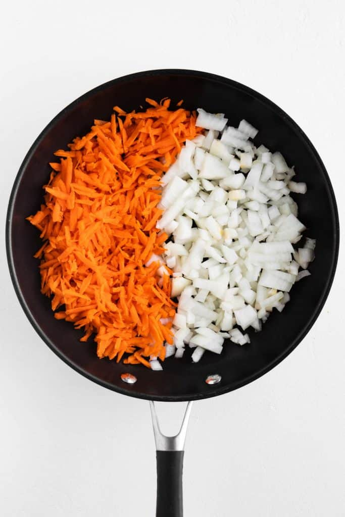 shredded carrot and diced onion in a black frying pan