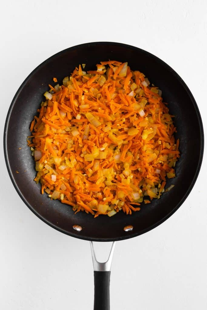 sauteed grated carrot and diced onion in a frying pan
