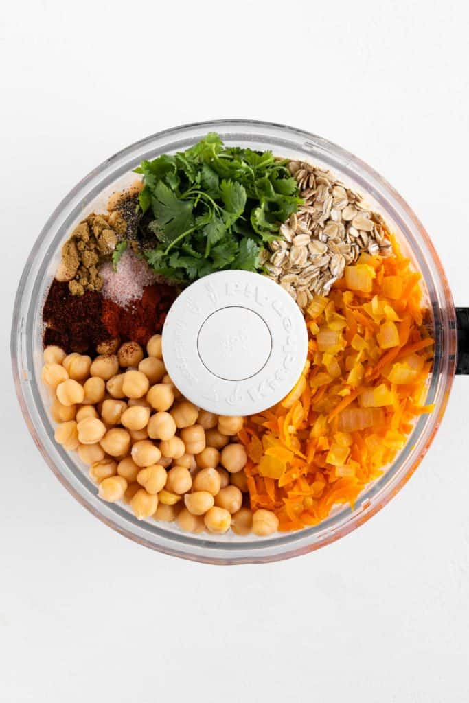 chickpeas, oats, grated carrots, diced onion, cilantro, and spices in a food processor bowl