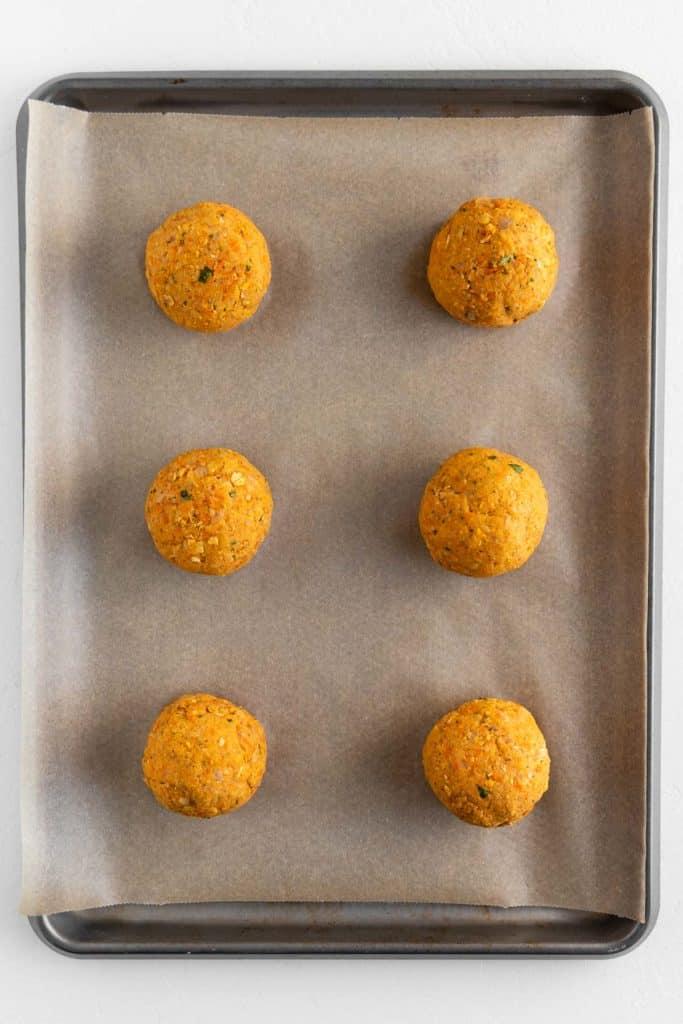 six balls of chickpea burger dough on a baking sheet