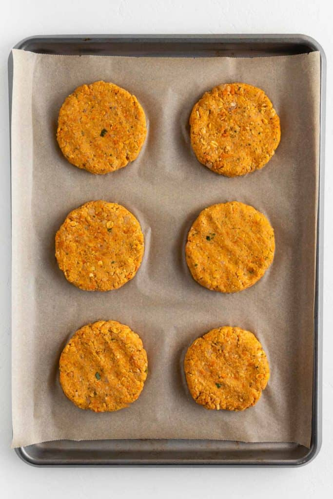 six uncooked vegan chickpea patties on a baking sheet