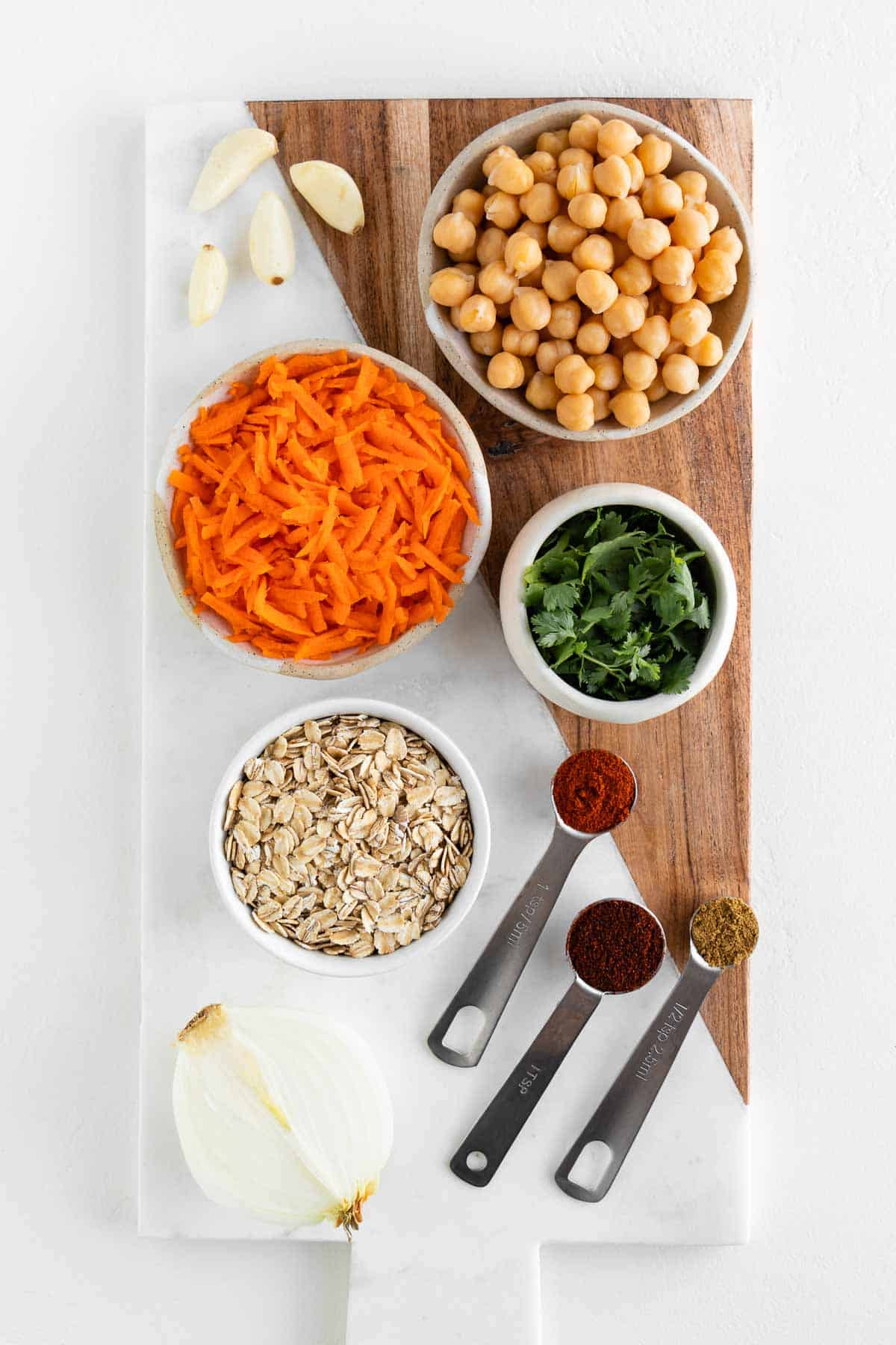 a marble and wooden cutting board topped with chickpeas, grated carrots, cilantro, rolled oats, onion, garlic, and spices