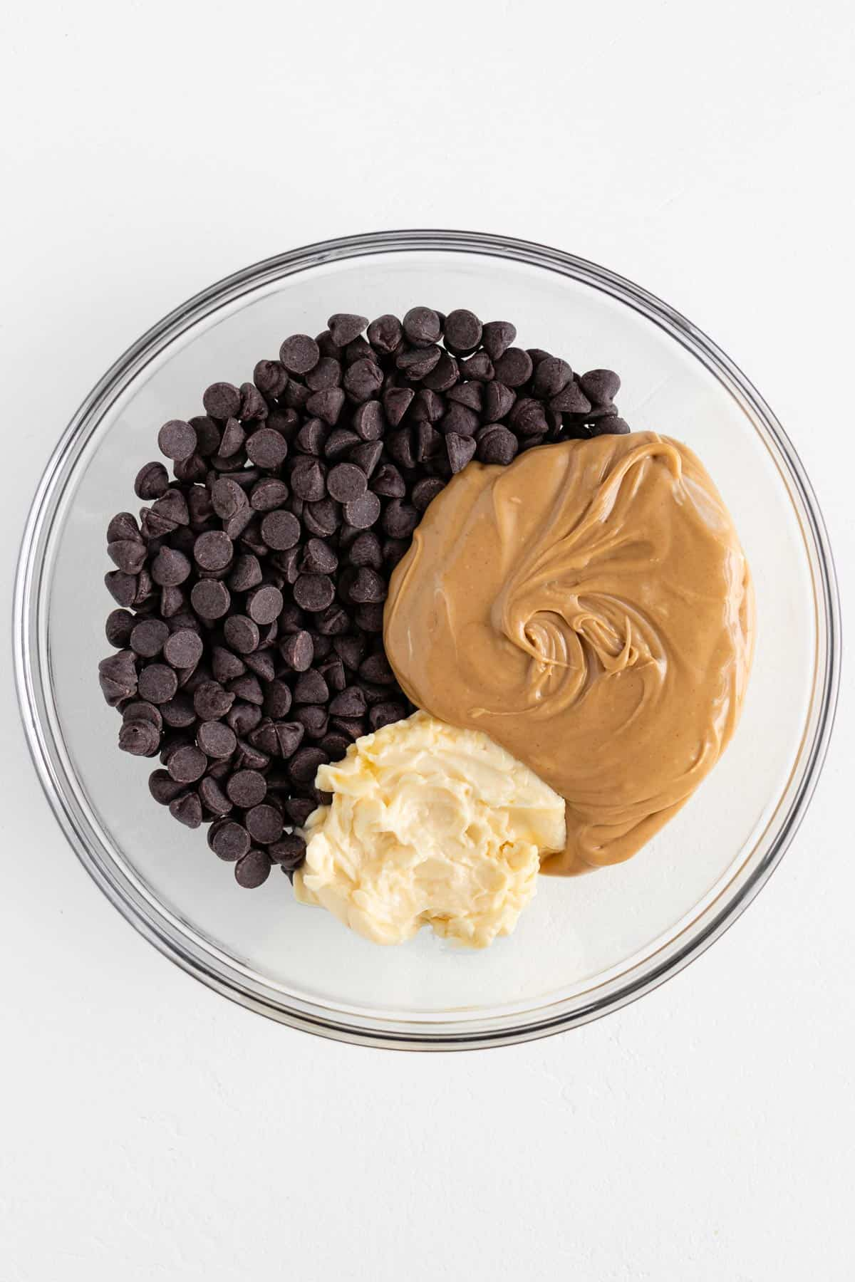 chocolate chips, vegan butter, and peanut butter inside a glass mixing bowl