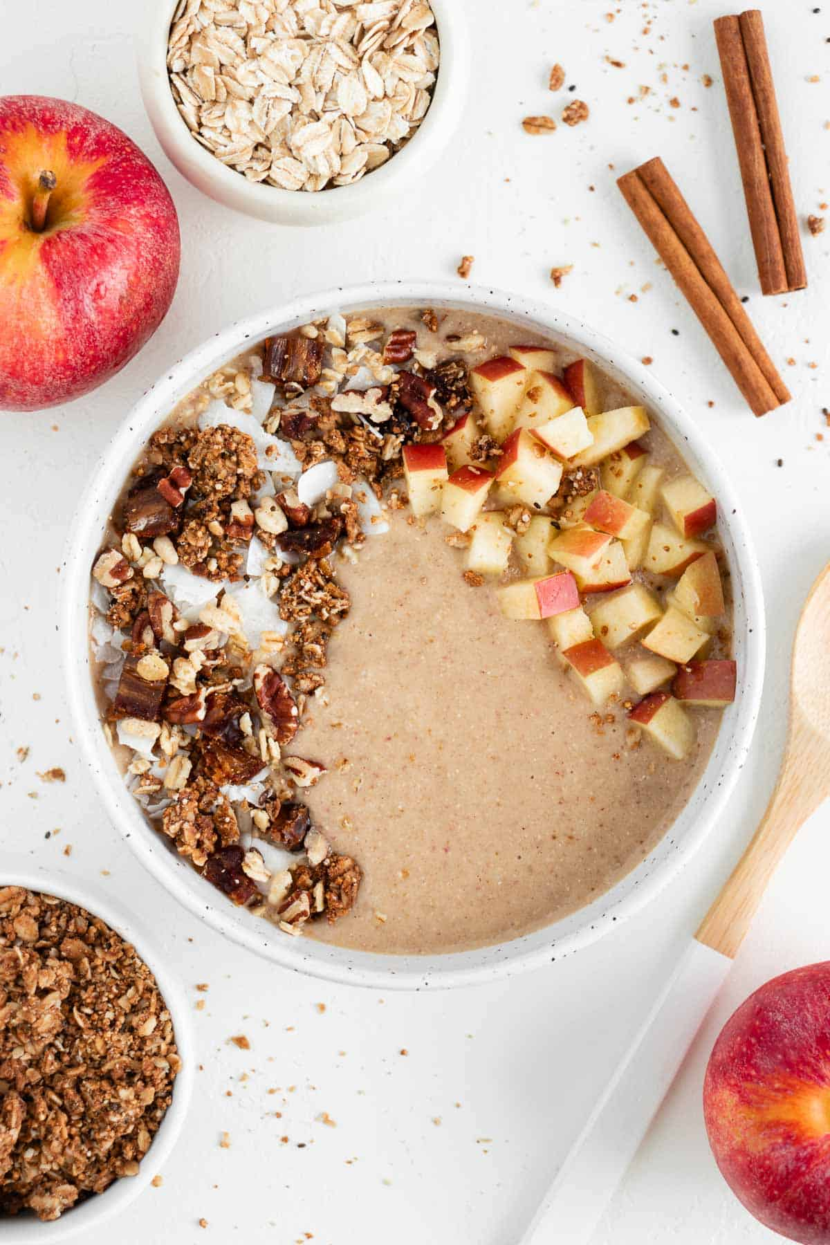an apple pie smoothie bowl in a ceramic bowl surrounded by apples, oats, granola, and cinnamon sticks