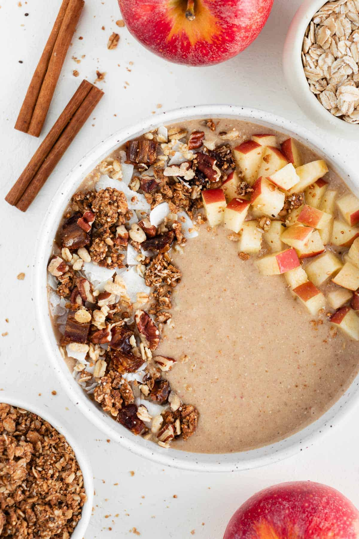 an apple pie smoothie bowl inside a ceramic bowl surrounded by oats, granola, cinnamon sticks, and apples