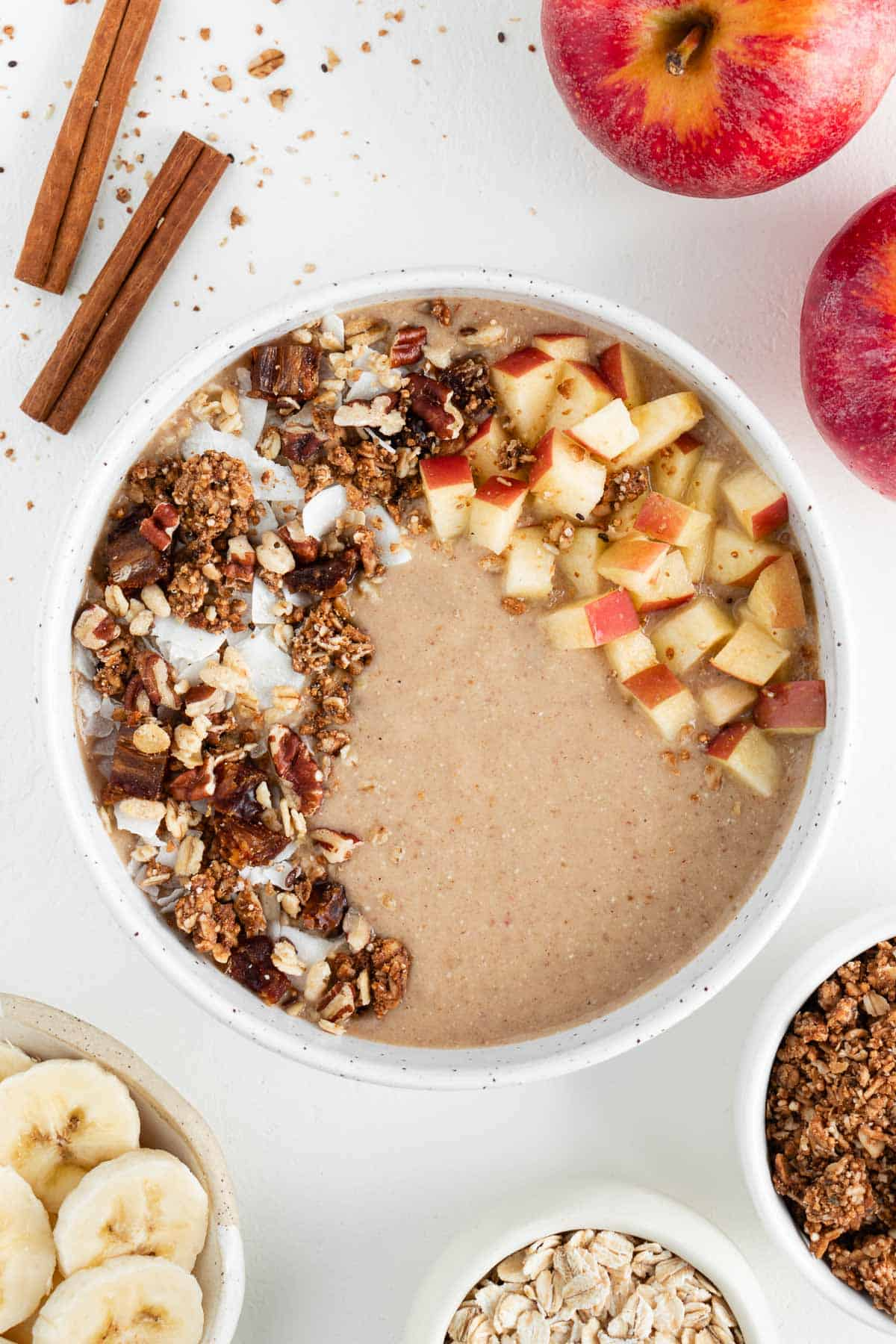 apple pie smoothie bowl surrounded by cinnamons ticks, apples, sliced banana, oats, and granola
