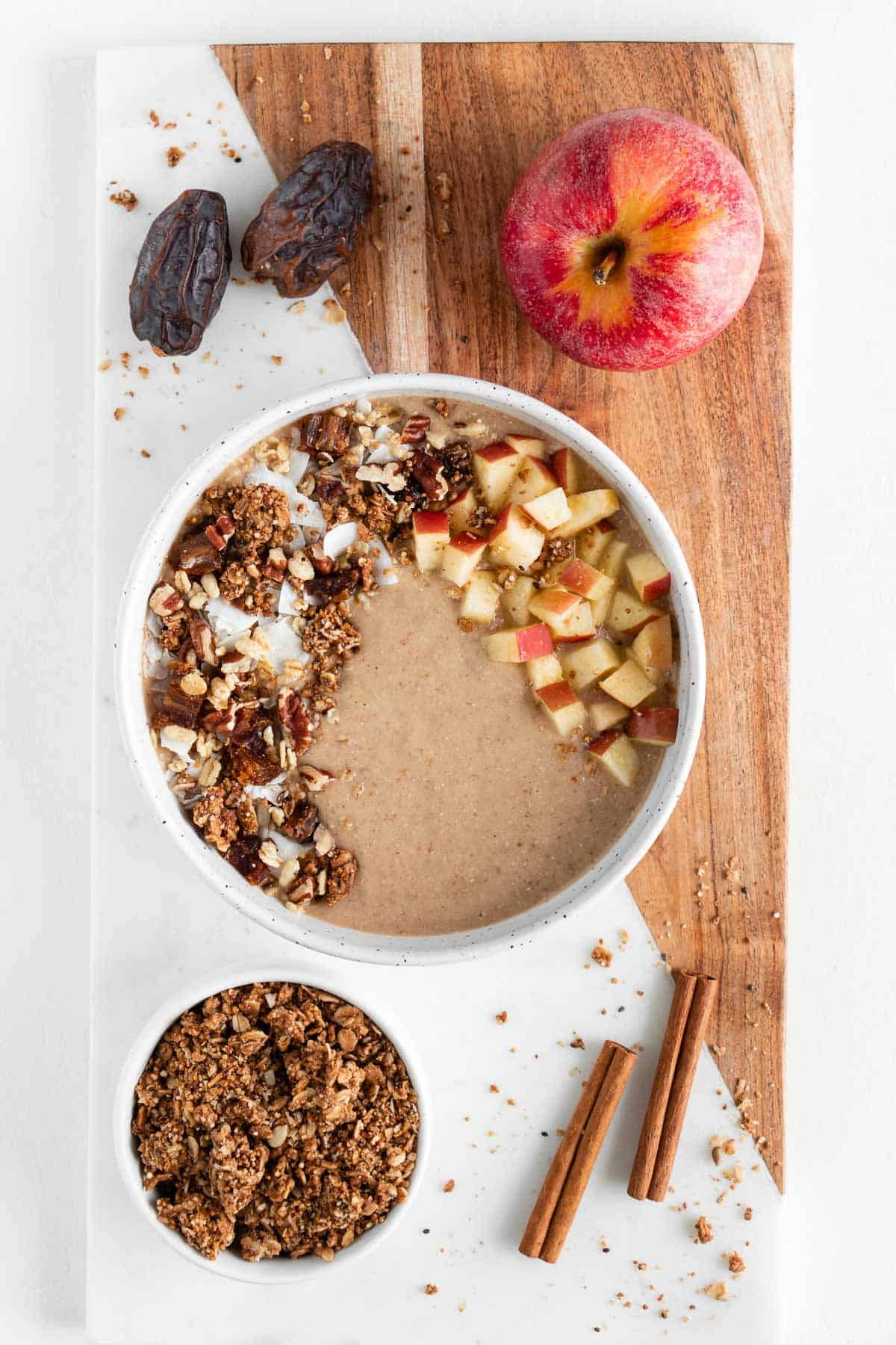 apple pie smoothie bowl, granola, apples, medjool dates, and cinnamon sticks on a marble board
