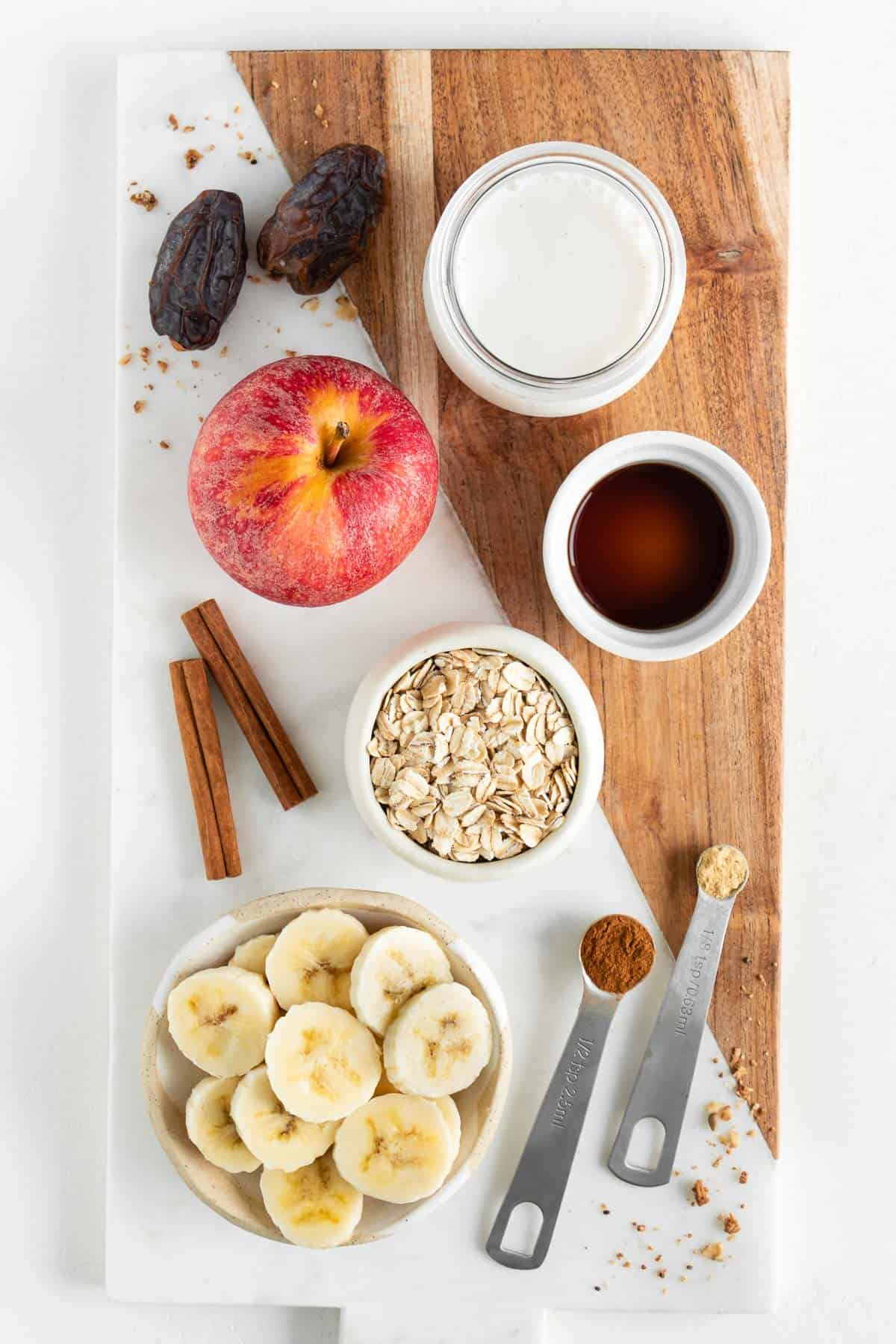 a marble board topped with an apple, oats, sliced banana, oat milk, medjool dates, cinnamon sticks, and vanilla extract