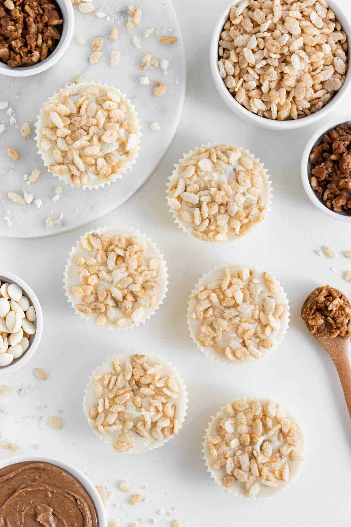 white chocolate almond butter cups surrounded by brown rice crisps cereal, nut butter, chocolate chips, and a wooden spoon