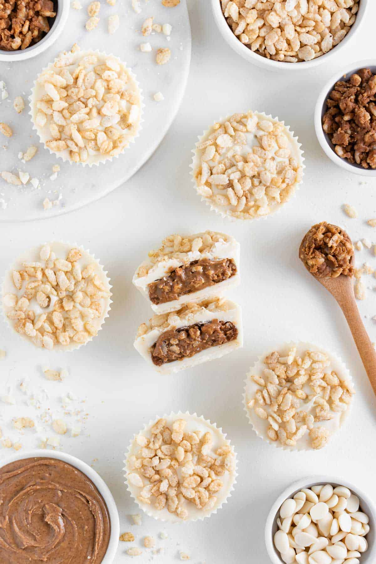 a crispy white chocolate almond butter cup cut in half surrounded by brown rice crisps cereal, chocolate chips, and nut butter