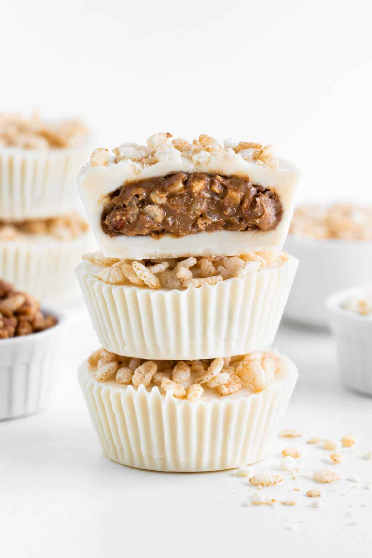 a stack of three crispy white chocolate almond butter cups with a bite taken out of the top one