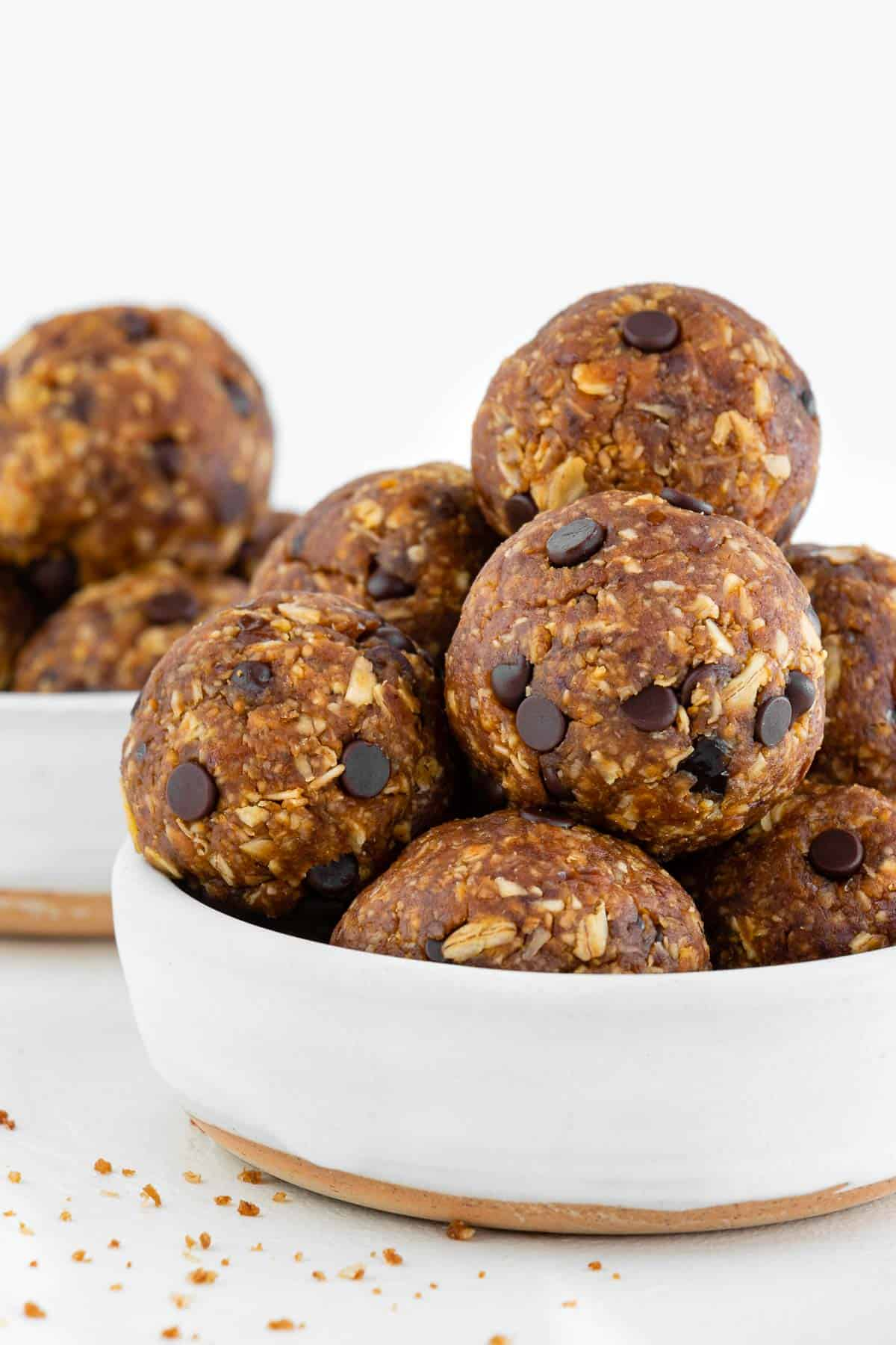 chocolate chip pumpkin energy balls stacked inside two white bowls