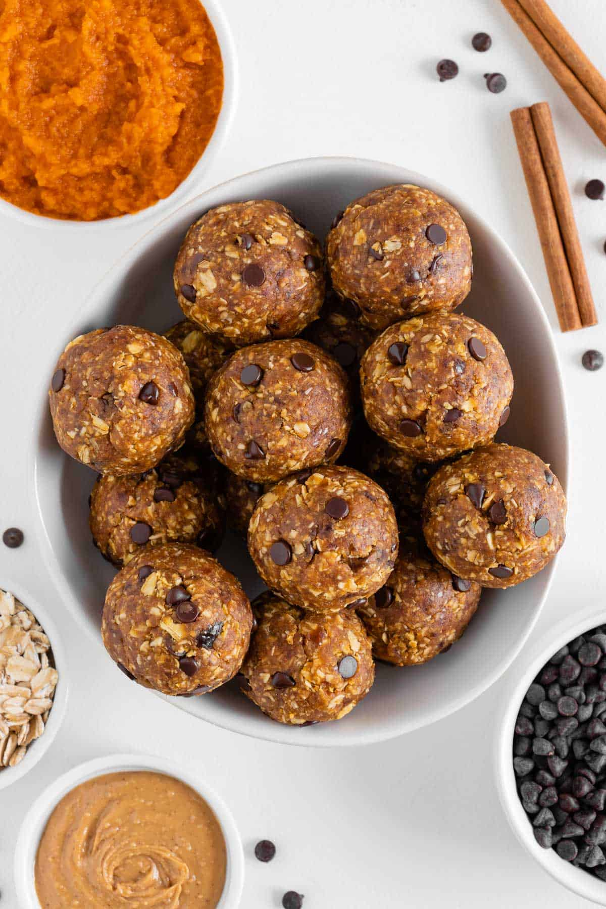pumpkin energy balls in a white bowl surrounded by pumpkin puree, peanut butter, chocolate chips, and oats