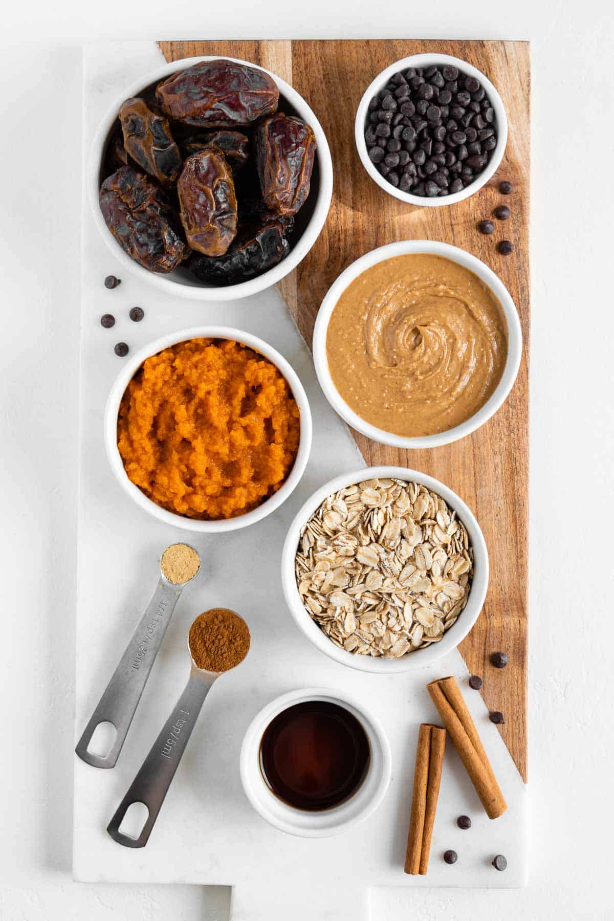 bowls filled with pumpkin puree, medjool dates, peanut butter, oats, vanilla extract, and chocolate chips on a wooden marble board