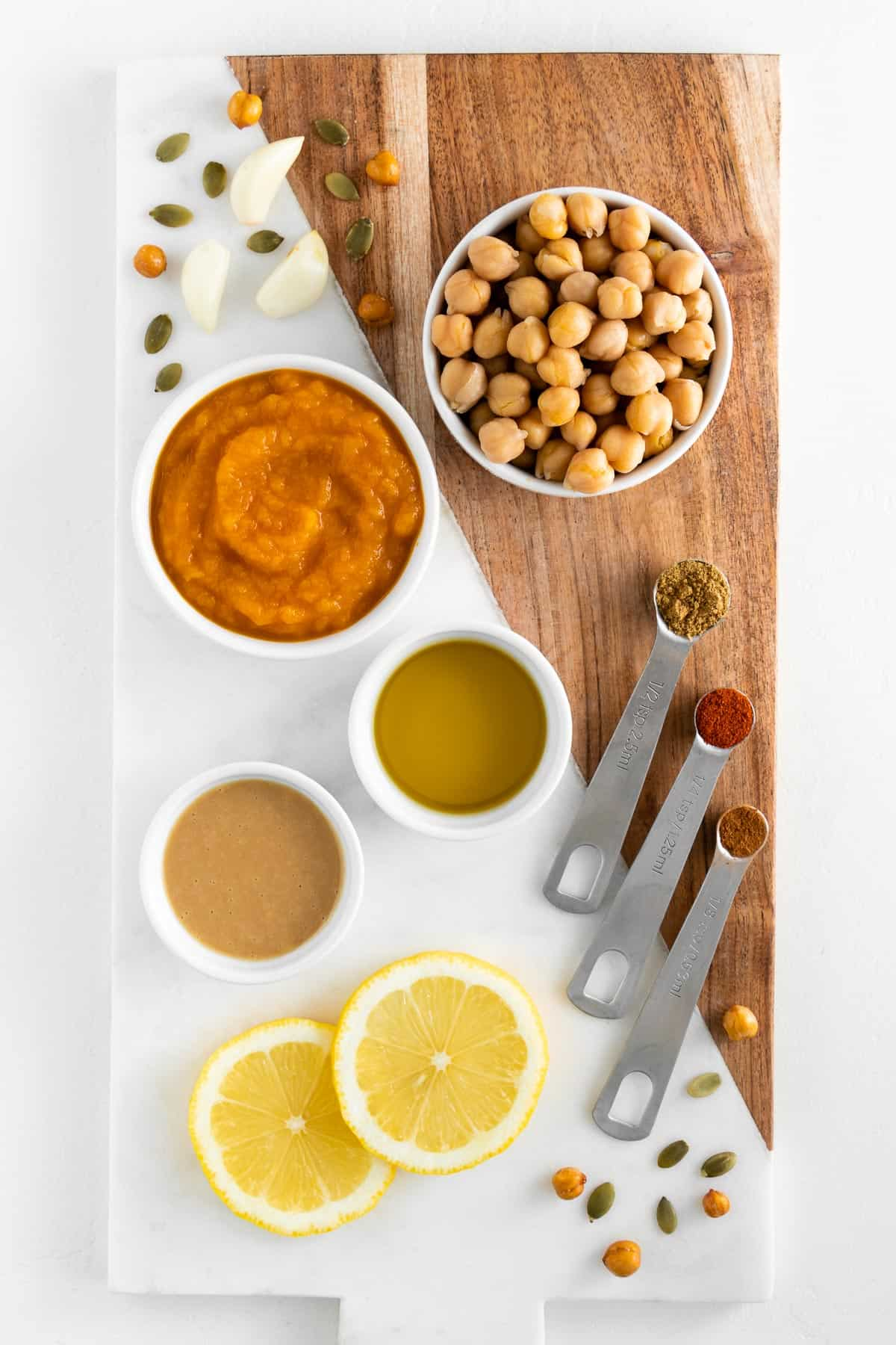 a marble and wood board topped with bowls of chickpeas, pumpkin puree, olive oil, tahini, sliced lemon, cumin, paprika, and cinnamon