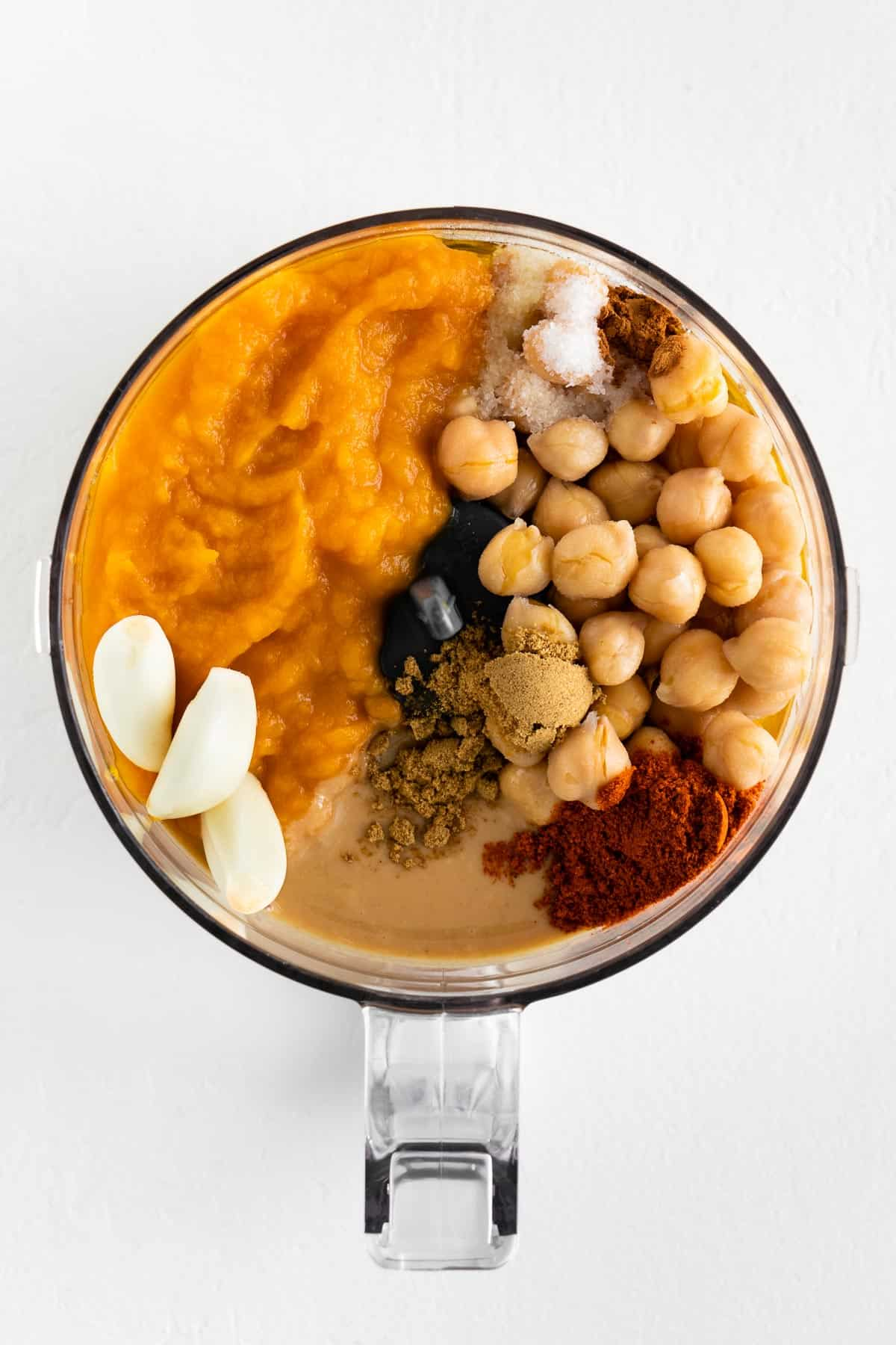 pumpkin puree, garbanzo beans, garlic cloves, cumin, paprika, cinnamon, salt, and tahini inside a food processor
