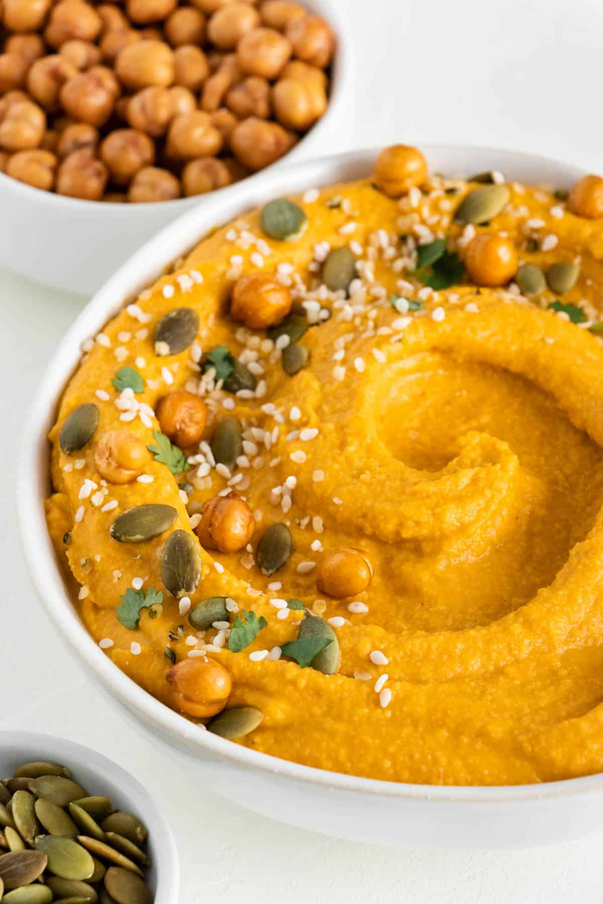 pumpkin hummus in a white bowl topped with chickpeas, pumpkin seeds, and sesame seeds