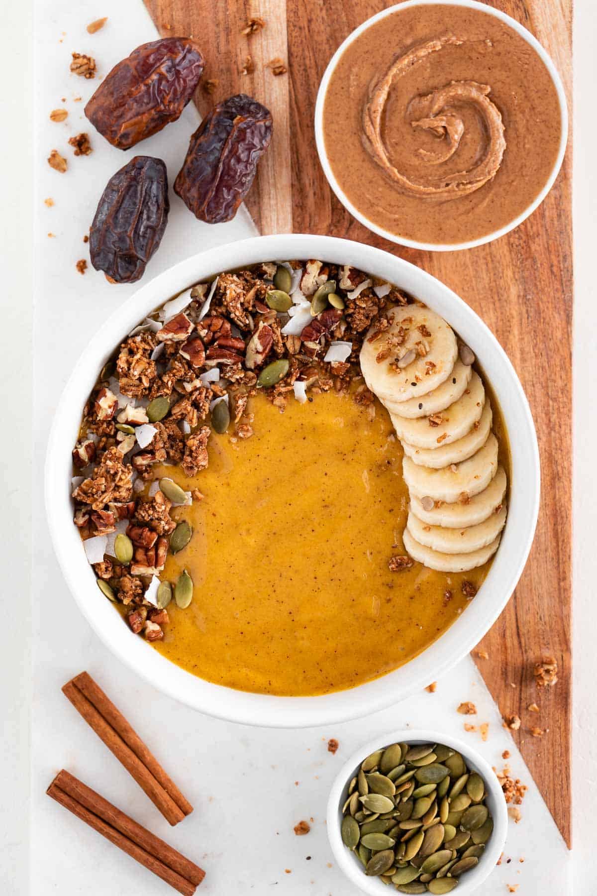 a pumpkin pie smoothie bowl on top of a marble cutting board along with medjool dates, almond butter, and pumpkin seeds