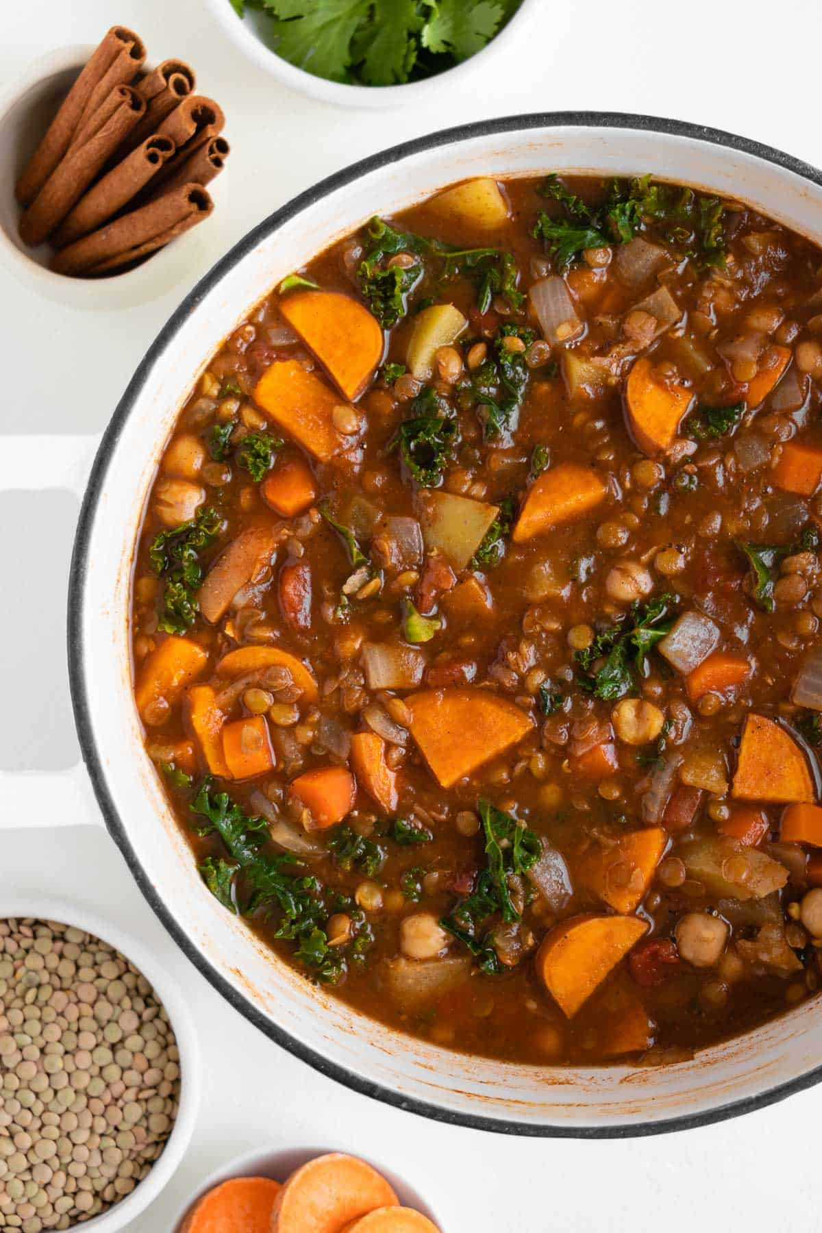 a large white pot filled with sweet potato, chickpea, and lentil stew