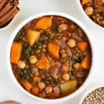 vegan moroccan stew inside two bowls beside fresh cilantro, green lentils, cinnamon, and sliced sweet potato