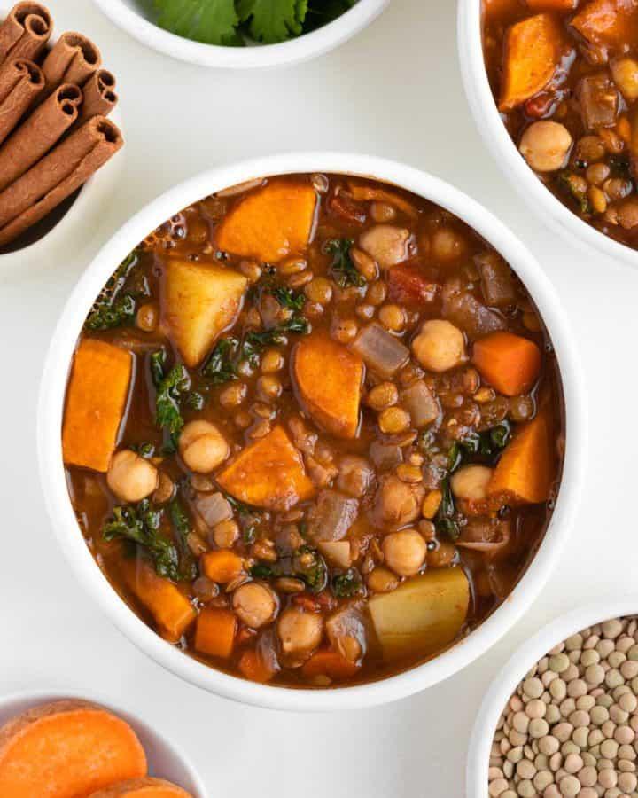 vegan moroccan stew inside two bowls beside fresh cilantro, green lentils, cinnamon, and sliced sweet potato