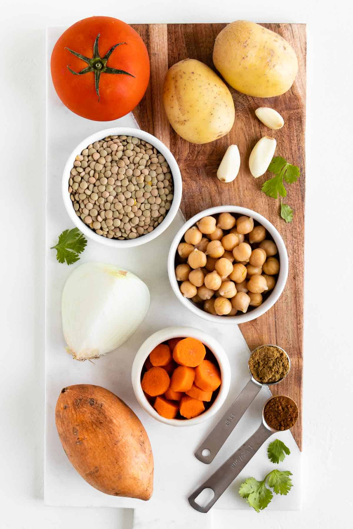 a small bowl of green lentils, chickpeas, and carrots on a marble board along with sweet potatoes, gold potatoes, tomato, and spices