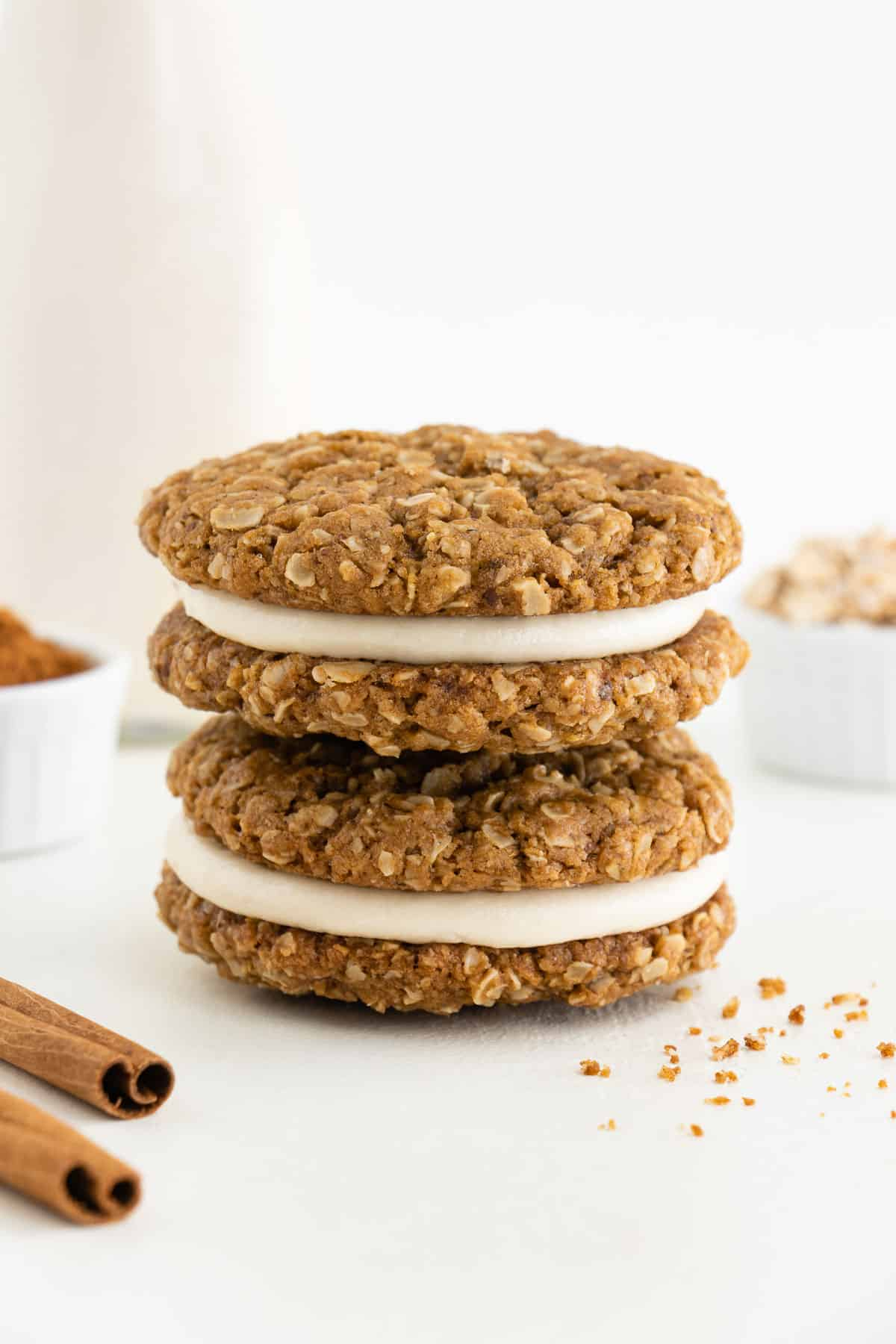a stack of two vegan oatmeal cream pie cookies beside a jar of almond milk, a bowl of oats, and cinnamon