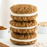 a stack of three vegan oatmeal cream pie cookies beside a jar of almond milk, a bowl of oats, and cinnamon