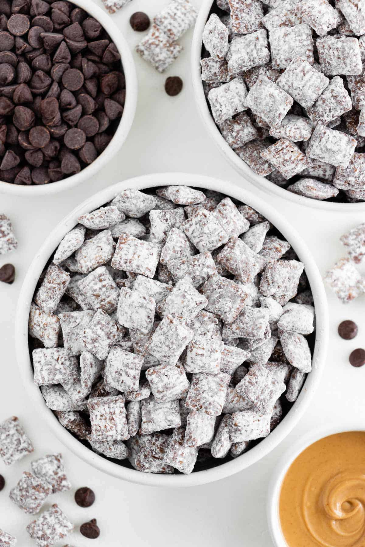 two bowls of vegan puppy chow surrounded by a bowl of chocolate chips and peanut butter