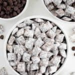 two bowls of vegan puppy chow surrounded by a bowl of chocolate chips and powdered sugar