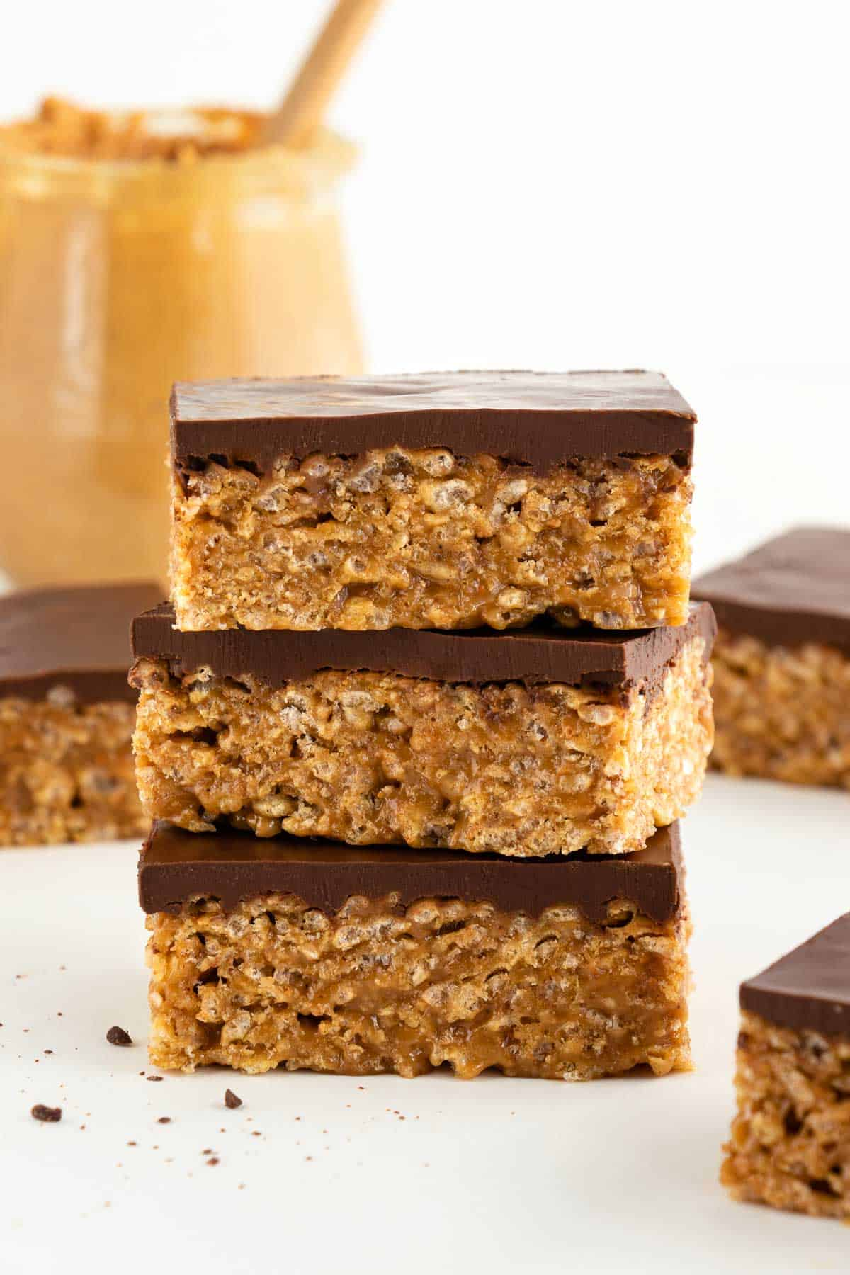 three vegan scotcheroos stacked on top of each other, surrounded by more vegan special k bars and a jar of peanut butter