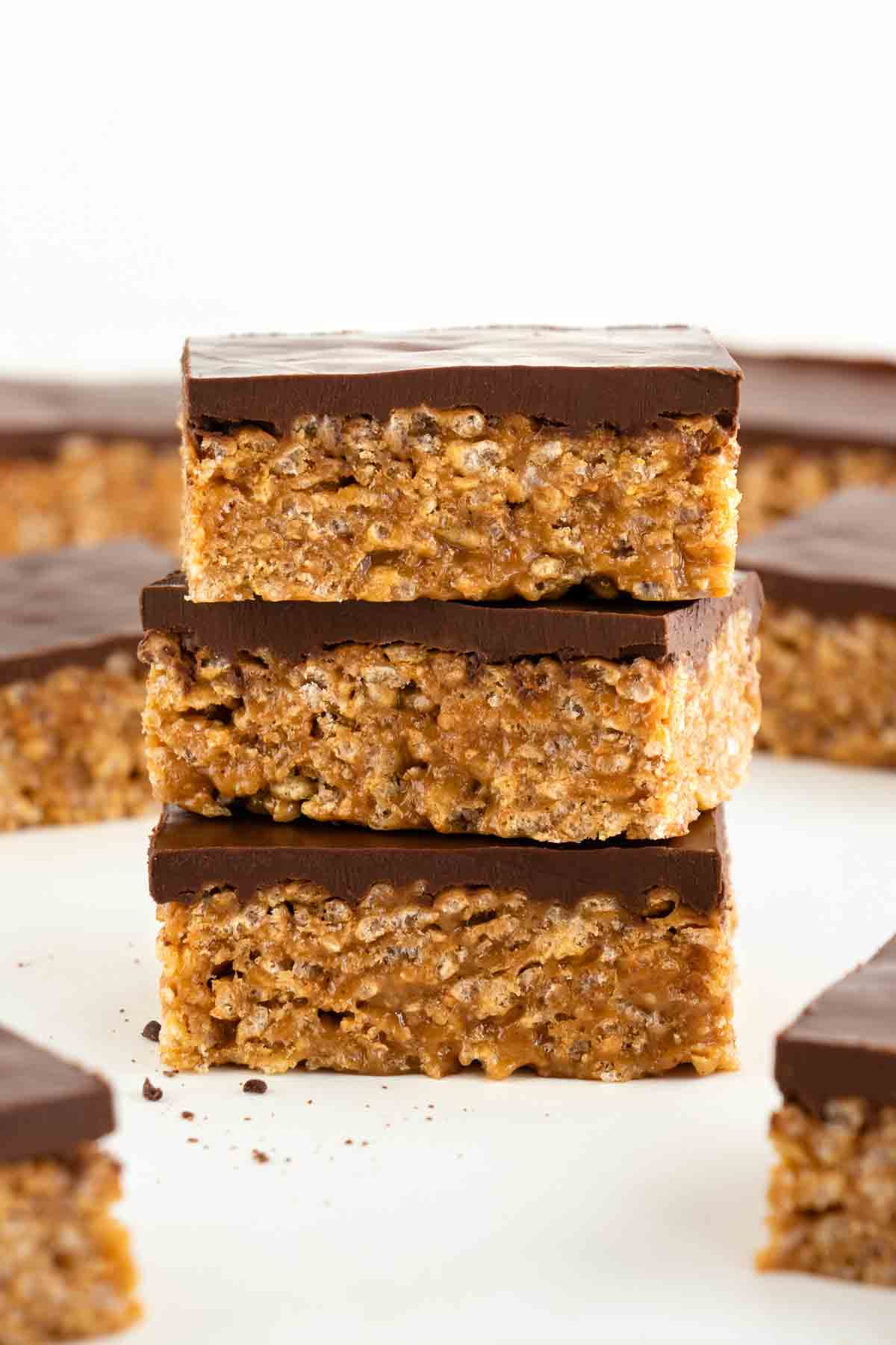 three vegan scotcheroos stacked on top of each other, surrounded by more vegan special k bars
