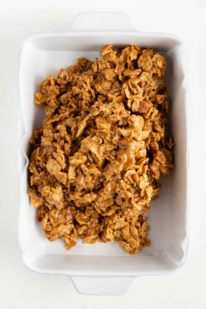 special k cereal mixed with brown rice syrup and peanut butter, placed inside a parchment lined white baking dish