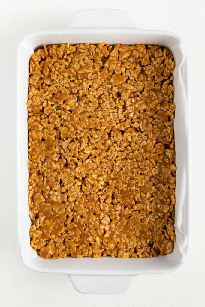 special k cereal mixed with brown rice syrup and peanut butter, pressed across the base of a rectangular white baking dish