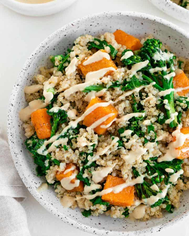 a butternut squash quinoa bowl with kale and broccoli, placed inside a ceramic dish beside a bowl of cashew cream