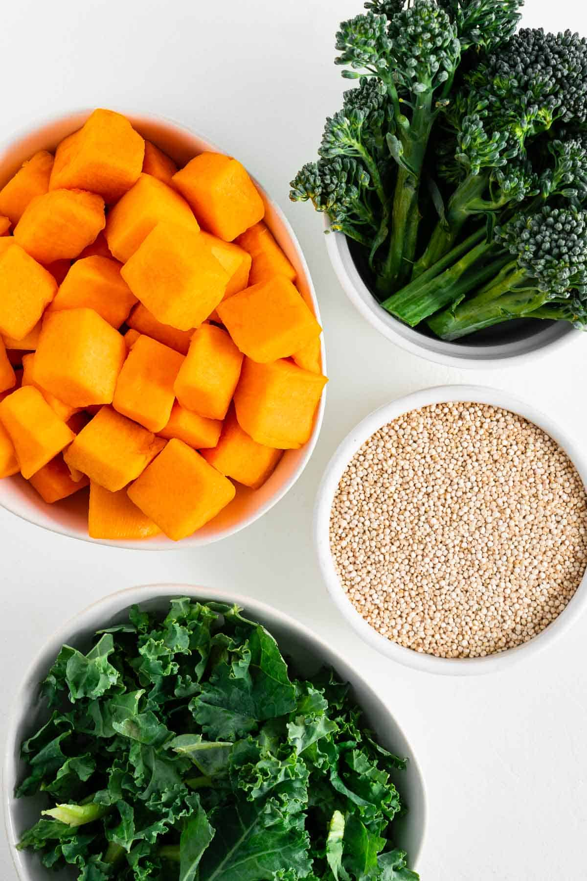 four white bowls filled with cubed butternut squash, broccolini, quinoa, and chopped kale