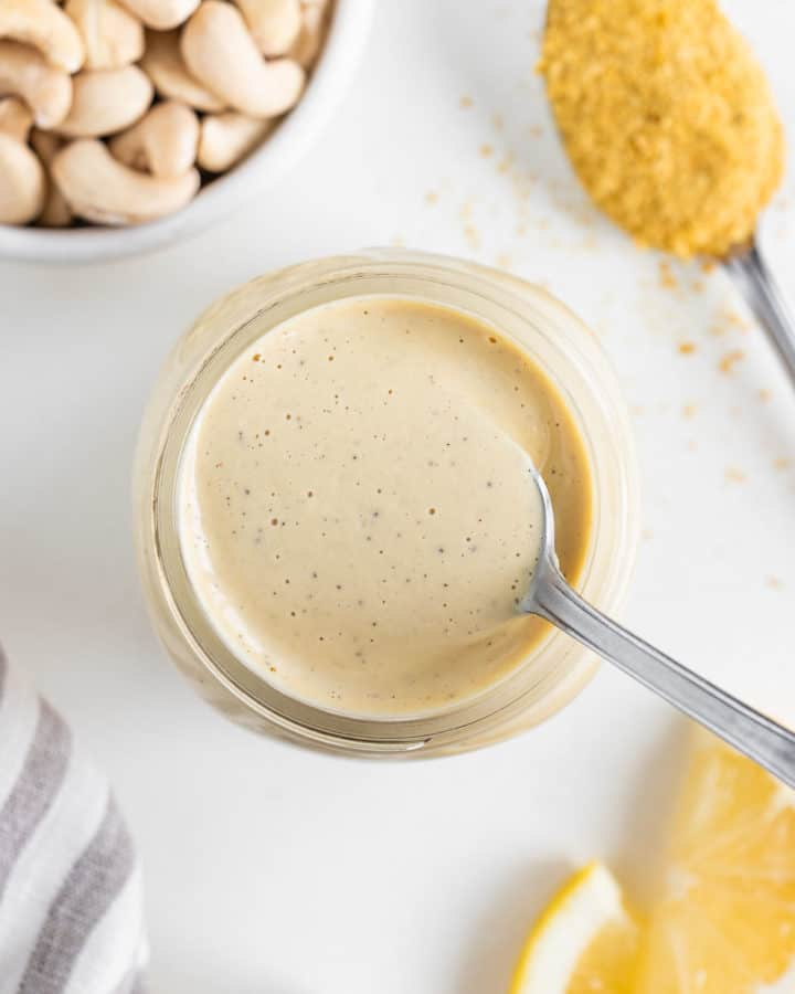 a spoon scooping into a jar of vegan cashew cream sauce