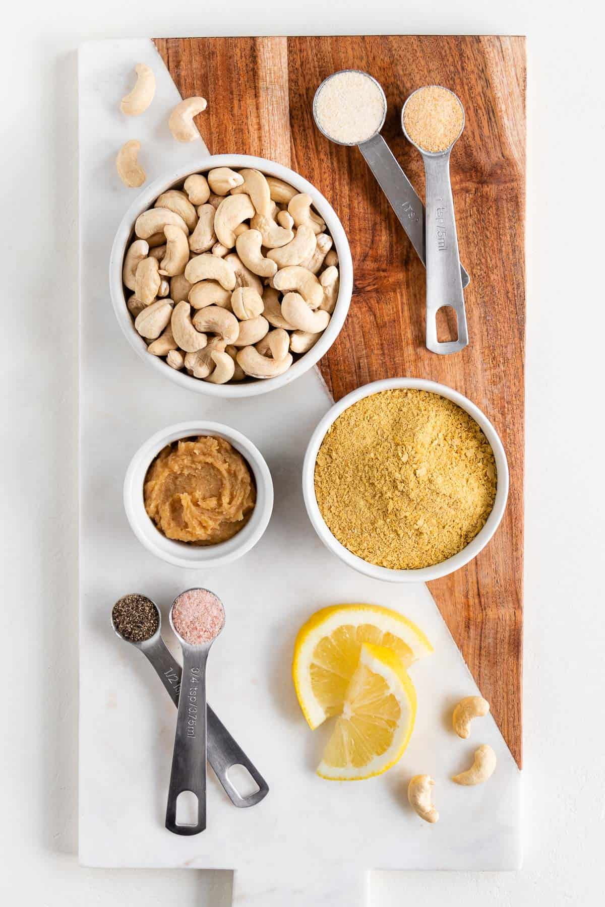 a wood and marble cutting board topped with bowls of cashews, nutritional yeast, white miso paste, salt, pepper, and lemon slices