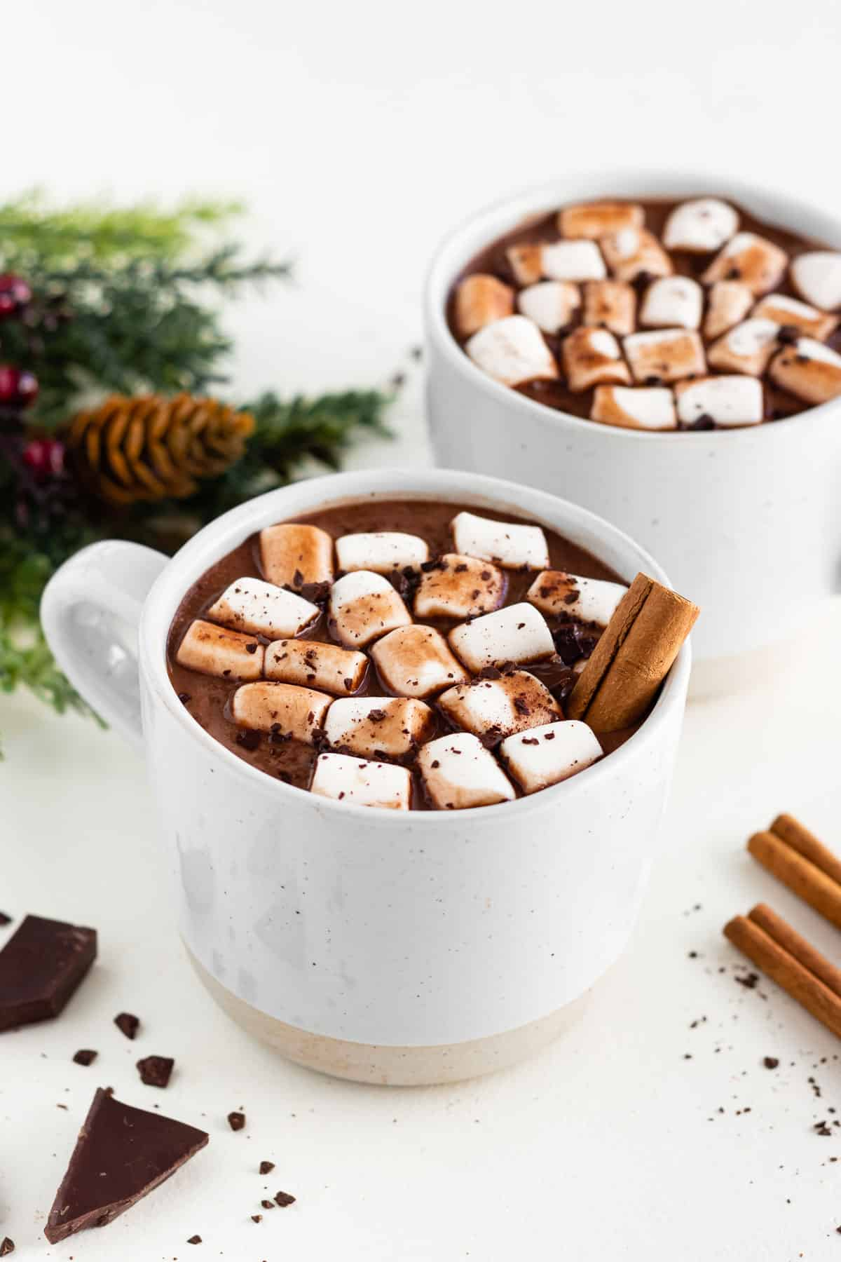 two ceramic mugs filled with vegan hot chocolate, mini marshmallows, and cinnamon