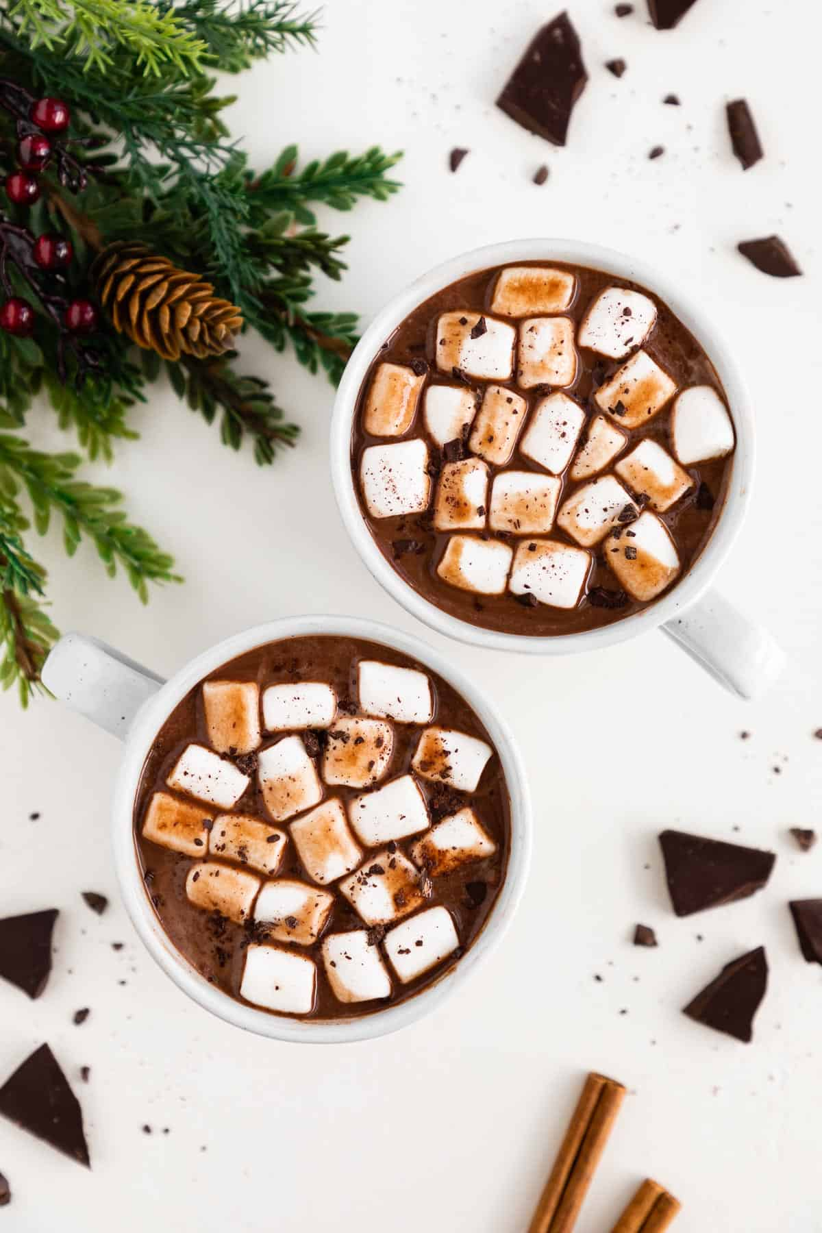 two white mugs filled with vegan hot chocolate, mini marshmallows, and chocolate shavings, surrounded by pieces of dark chocolate