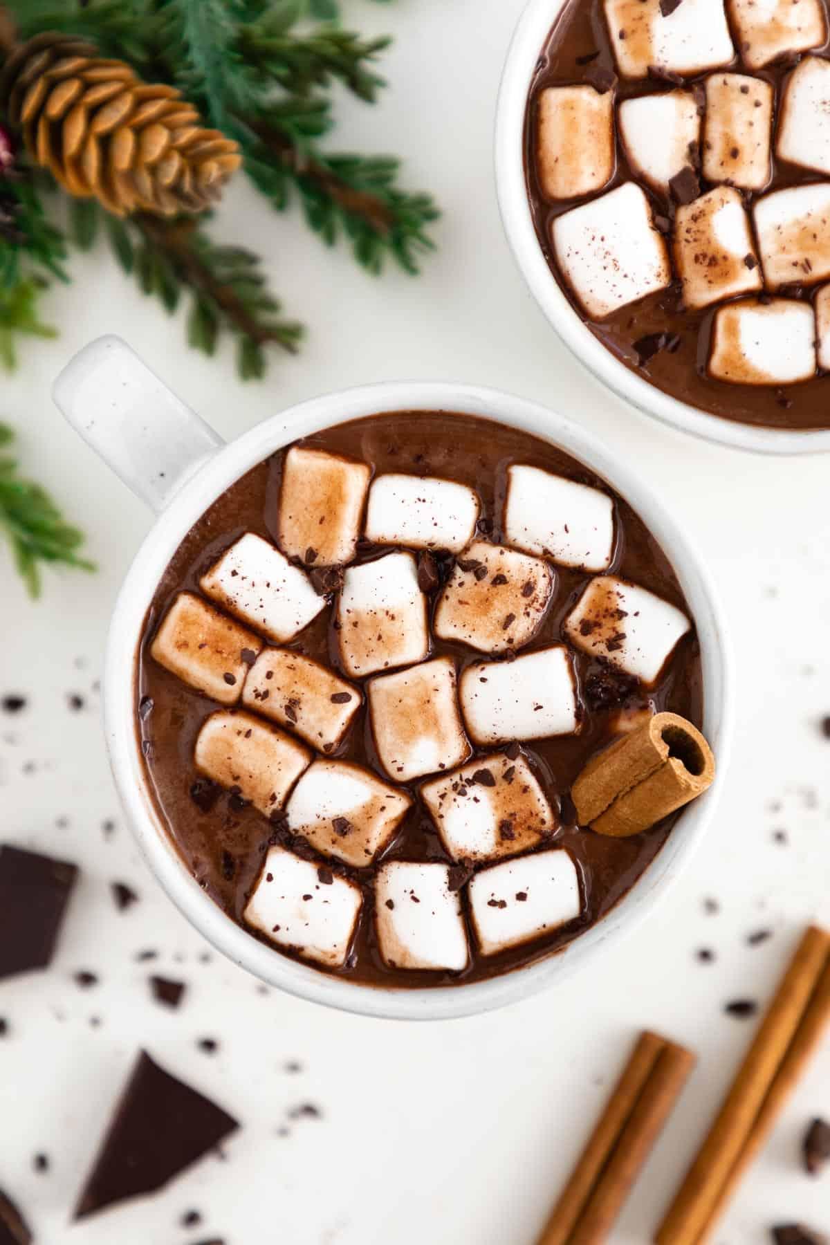 vegan hot chocolate inside a white ceramic mug topped with mini marshmallows and a cinnamon stick