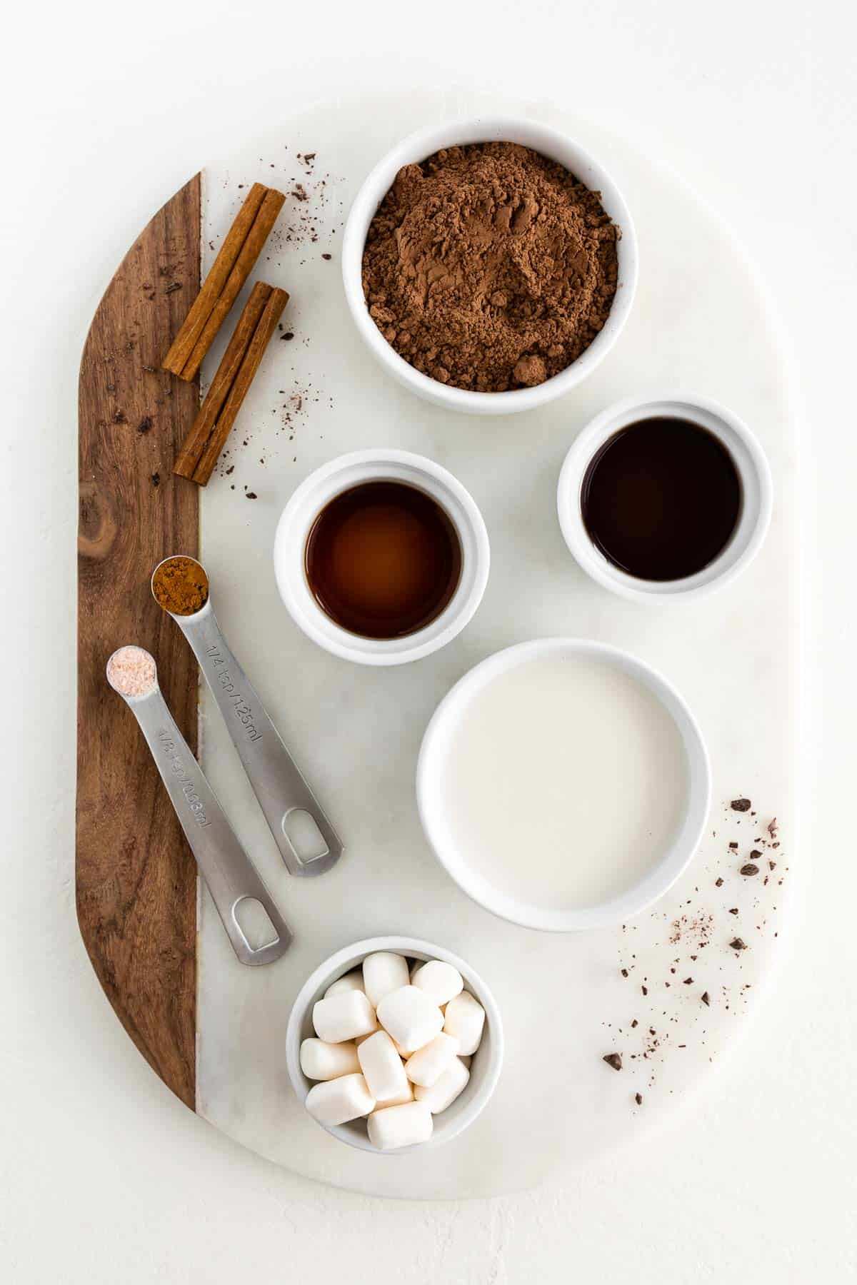 a marble board topped with bowls of cocoa powder, oat milk, vanilla extract, maple syrup, marshmallows, and cinnamon sticks