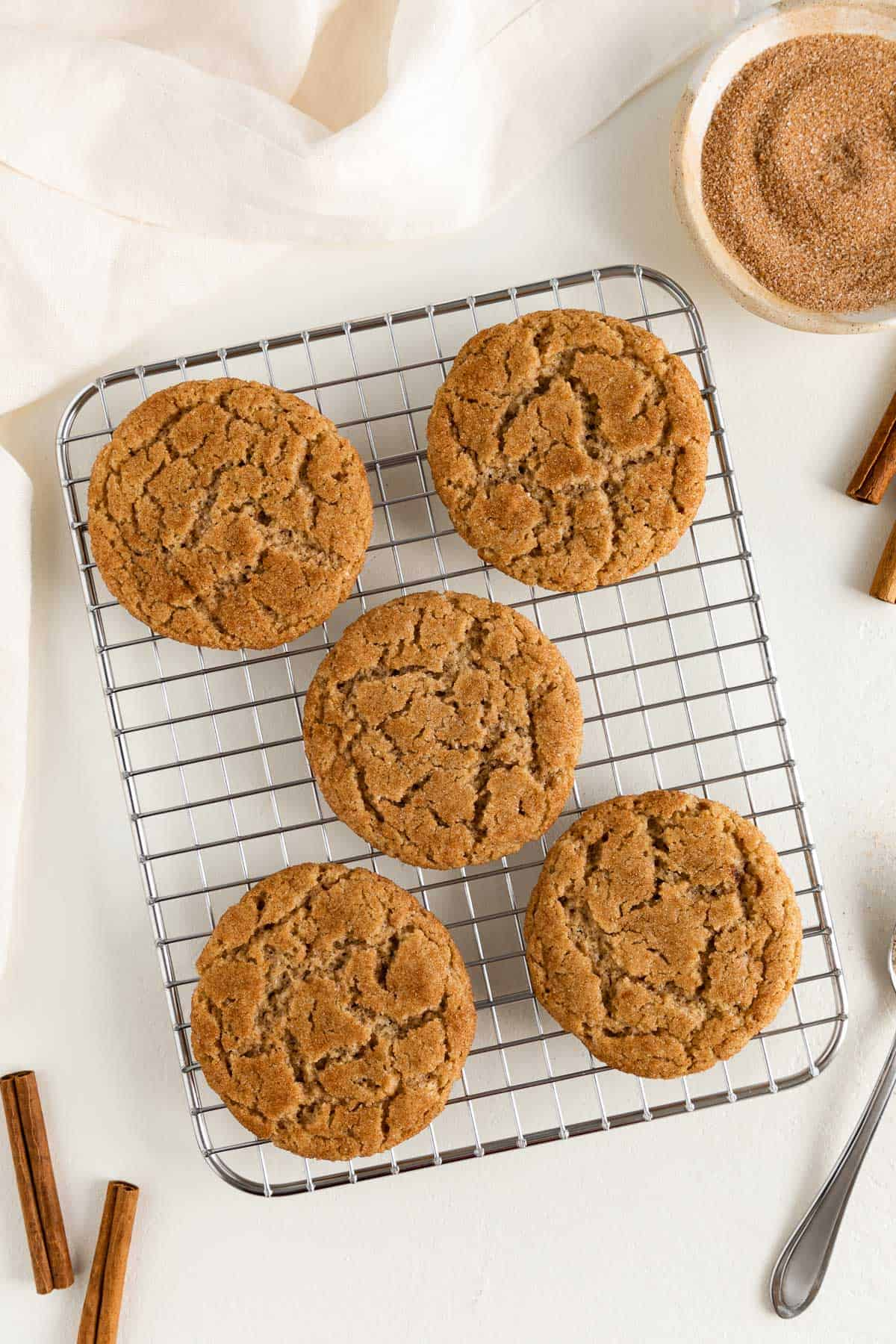 five vegan snickerdoodle cookies resting on a wire cooling rack placed beside a bowl of cinnamon sugar, cinnamon sticks, and a cream colored linen napkin