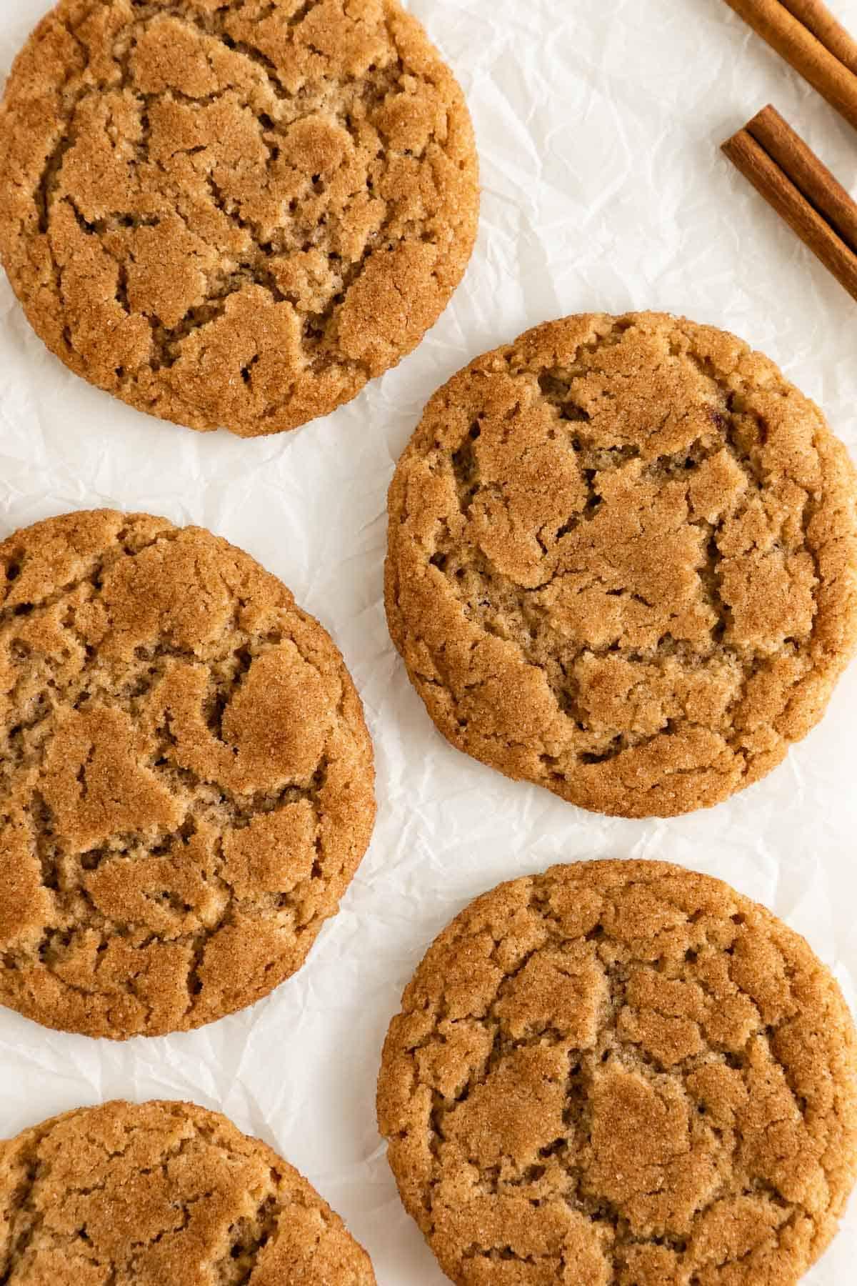 an overhead photo of five vegan snickerdoodle cookies beside two cinnamon sticks