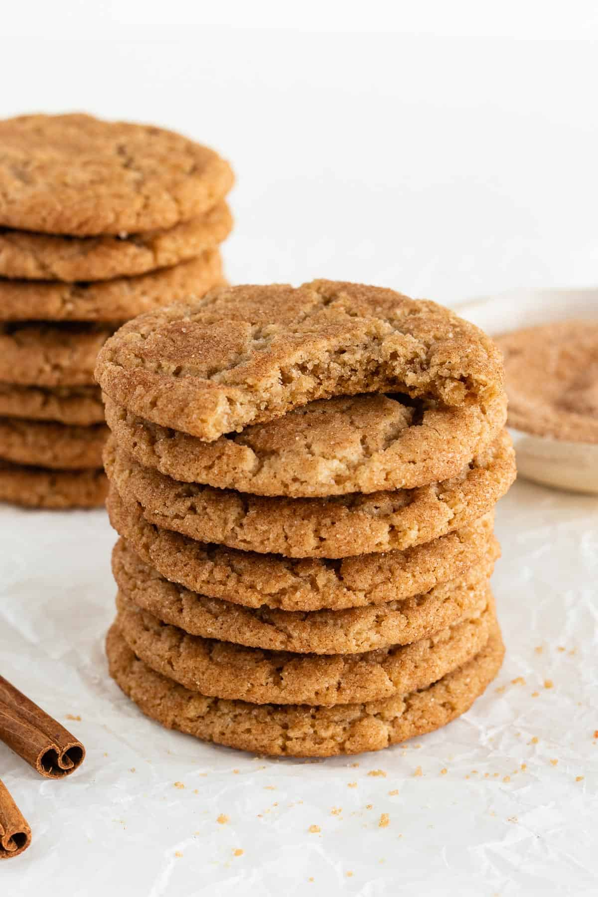 two tall stacks of vegan snickerdoodle cookies with a bite taken out of the top cookie