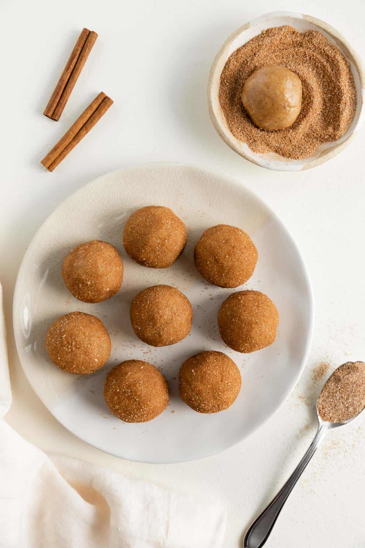 a plate topped with eight balls of vegan cookie dough rolled in cinnamon sugar