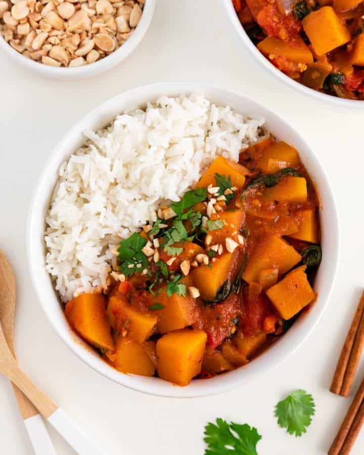 a bowl of butternut squash curry and white rice surrounded by another bowl of curry, a bowl filled with crushed peanuts, wooden spoons, and cinnamon sticks