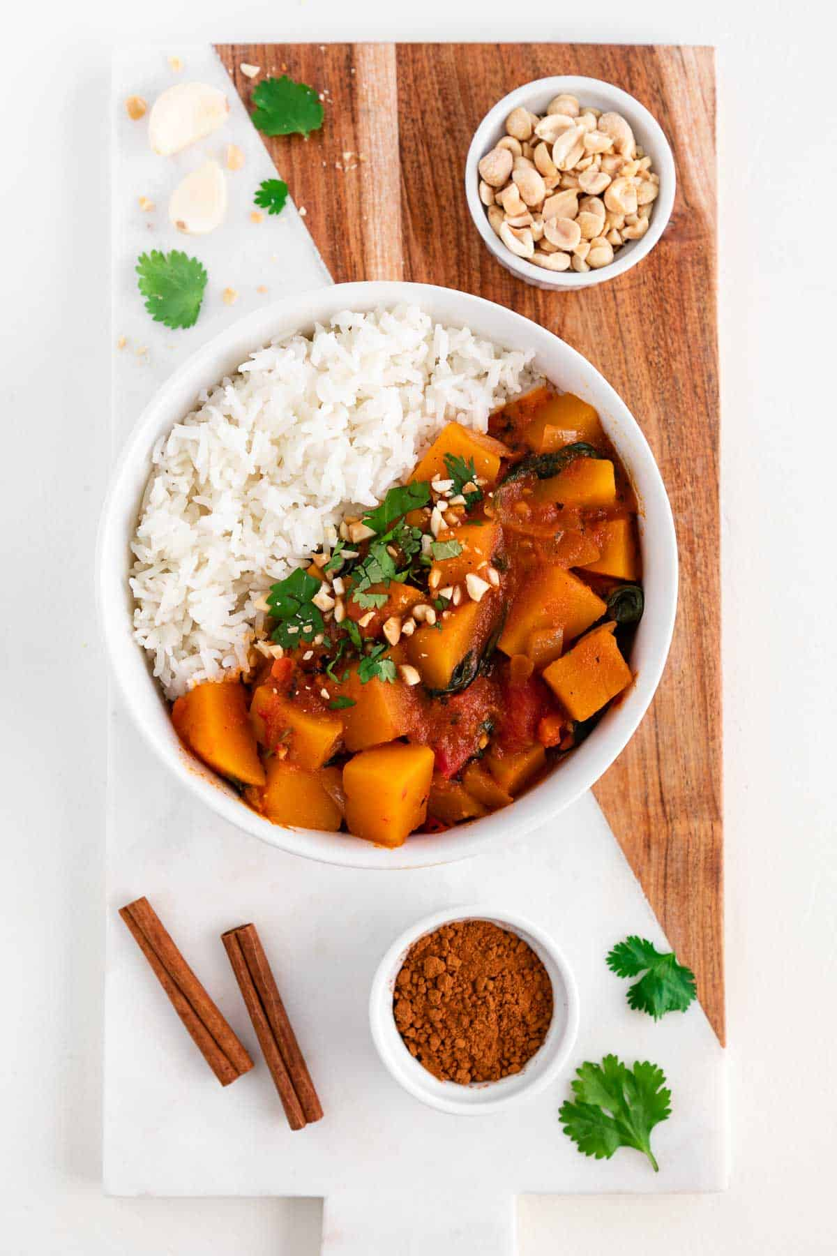 a wood and marble cutting board topped with a bowl of butternut squash curry, a bowl of peanuts, a bowl of cinnamon, and fresh cilantro